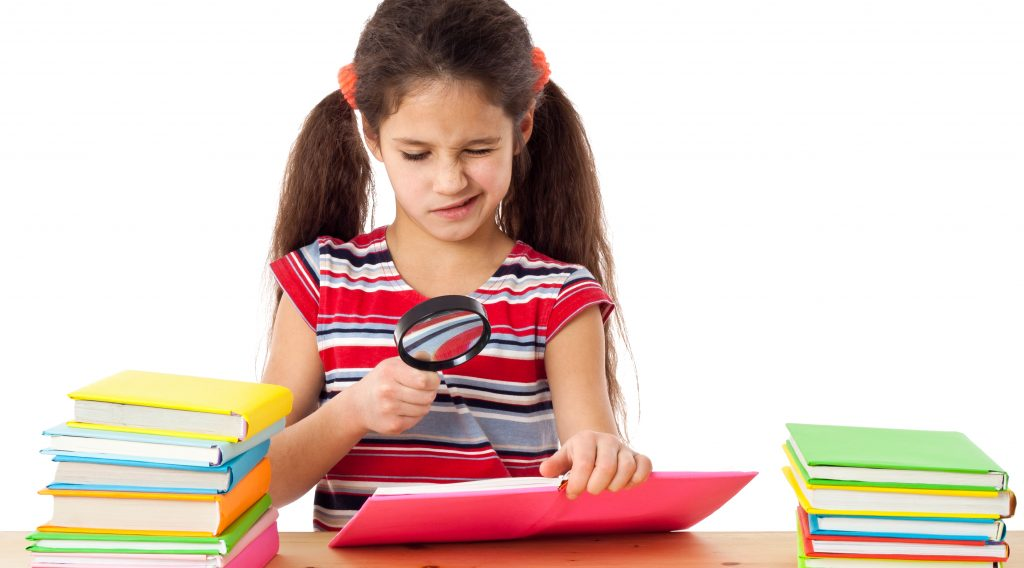 Girl reading the books on the desk with magnifying glass, isolated on white